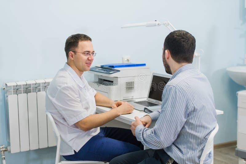 Αρσενικός γιατρός που συζητά τις εκθέσεις με τον ασθενή στο γραφείο στο ιατρικό γραφείο στοκ φωτογραφία