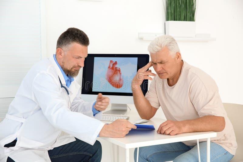 Αρσενικός γιατρός που συνεργάζεται με τον ασθενή στην κλινική στοκ εικόνες