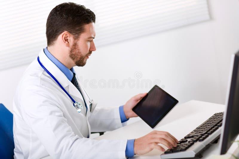 Αρσενικός γιατρός που χρησιμοποιεί την ταμπλέτα στοκ εικόνες