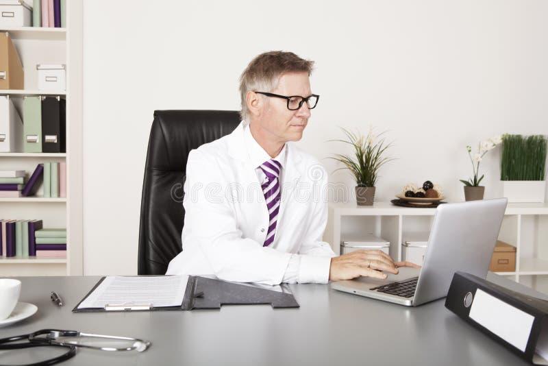 Αρσενικός γιατρός που χρησιμοποιεί το lap-top στοκ εικόνα με δικαίωμα ελεύθερης χρήσης