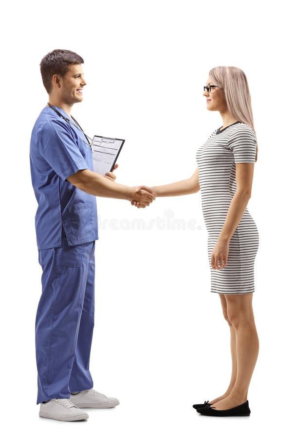 Αρσενικός γιατρός χέρια ενός στα μπλε ομοιόμορφα τινάγματος με μια νέα γυναίκα στοκ φωτογραφίες με δικαίωμα ελεύθερης χρήσης
