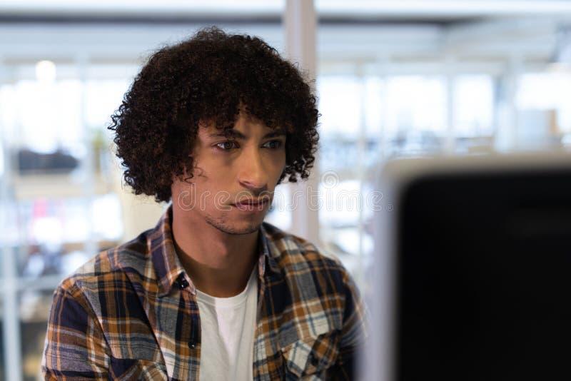 Αρσενικός γραφικός σχεδιαστής που εργάζεται στον υπολογιστή στοκ εικόνες
