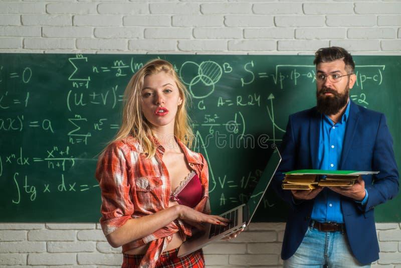 Αρσενικός δάσκαλος με τους σπουδαστές Νέος ελκυστικός δάσκαλος που δείχνει στον πίνακα κιμωλίας Προκλητική γυναίκα σπουδαστής που στοκ εικόνες