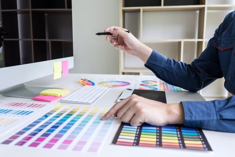 Αρσενικός δημιουργικός γραφικός σχεδιαστής που εργάζεται στην επιλογή χρώματος και ομο στοκ εικόνες