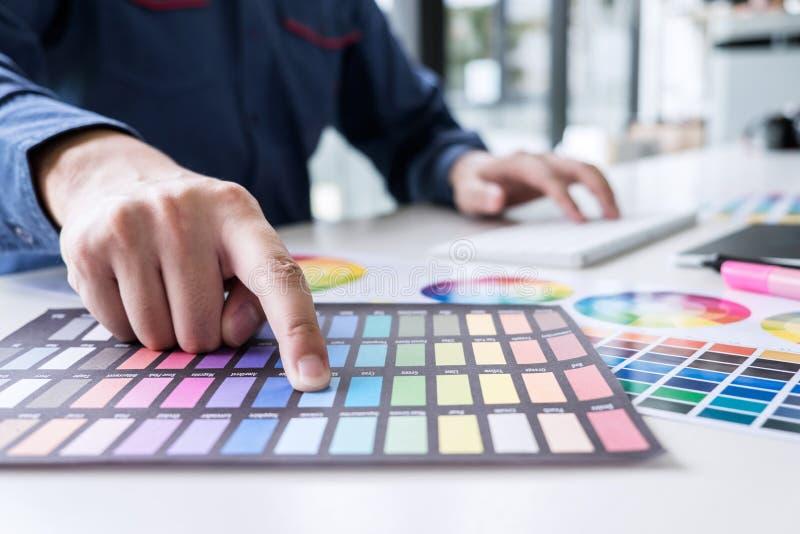 Αρσενικός δημιουργικός γραφικός σχεδιαστής που εργάζεται στην επιλογή χρώματος και ομο στοκ φωτογραφία