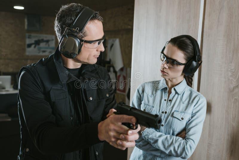 αρσενικός εκπαιδευτικός που περιγράφει το πυροβόλο όπλο στο θηλυκό πελάτη στοκ φωτογραφία με δικαίωμα ελεύθερης χρήσης