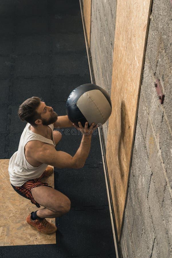 Αρσενικός εκπαιδευτής Crossfit που κάνει τη σφαίρα τοίχων στοκ εικόνες