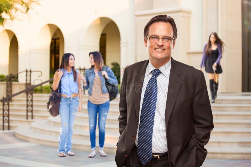 Αρσενικός ενήλικος διοικητής στο κοστούμι και δεσμός που περπατά στην πανεπιστημιούπολη στοκ φωτογραφία