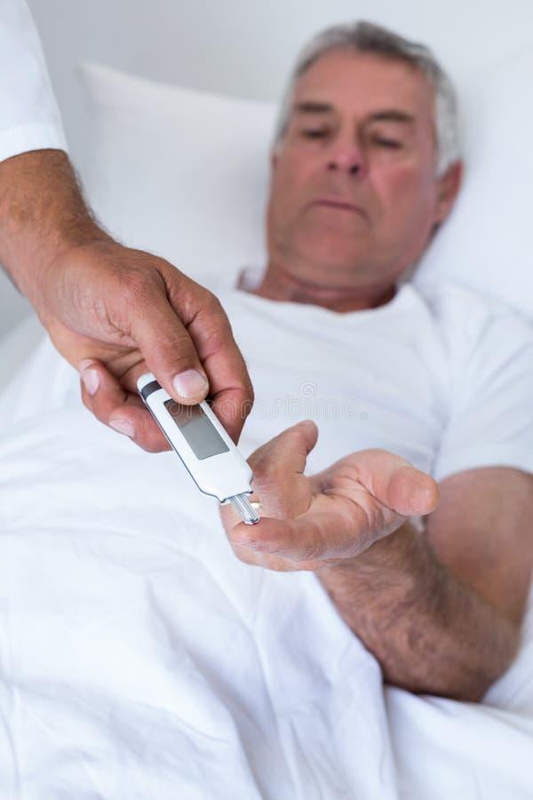 Αρσενικός εξεταστικός διαβήτης γιατρών του ανώτερου ατόμου στο μετρητή γλυκόζης στοκ εικόνες