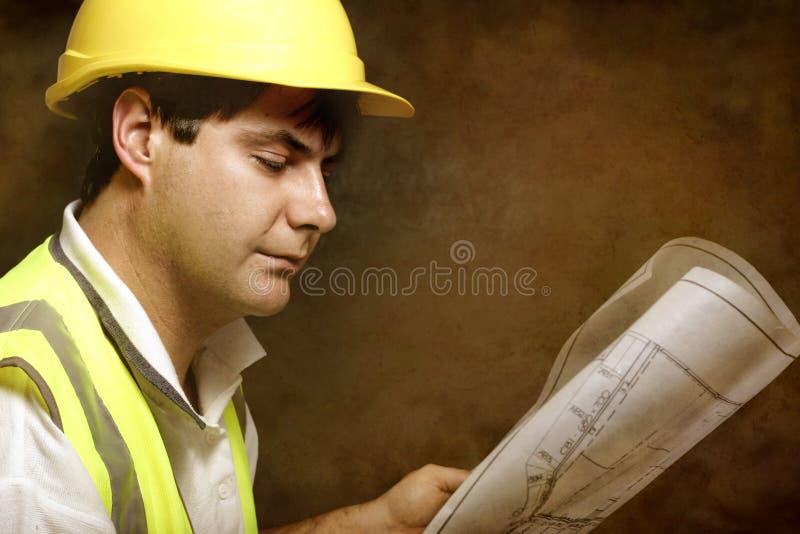 Αρσενικός επιστάτης περιοχών οικοδόμων που διαβάζει τα αρχιτεκτονικά βιομηχανικά σχέδια στοκ εικόνες