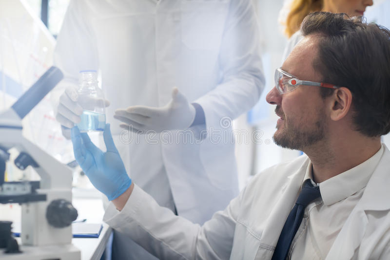 Αρσενικός επιστήμονας που συνεργάζεται με το μικροσκόπιο, την ομάδα στο εργαστήριο που κάνει την έρευνα, τον άνδρα και τη γυναίκα στοκ εικόνες