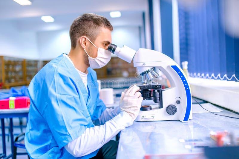 Αρσενικός επιστήμονας, φαρμακοποιός που εργάζεται με το μικροσκόπιο στο φαρμακείο στοκ φωτογραφία με δικαίωμα ελεύθερης χρήσης