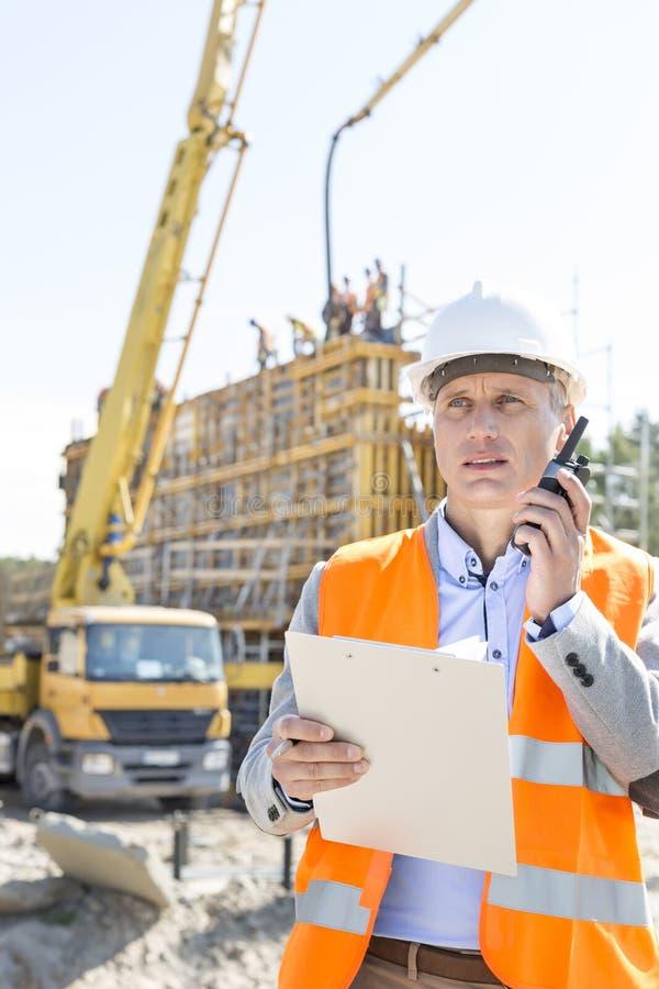 Αρσενικός επόπτης που χρησιμοποιεί walkie-talkie κρατώντας την περιοχή αποκομμάτων στο εργοτάξιο οικοδομής στοκ εικόνες