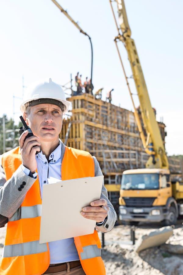 Αρσενικός επόπτης που χρησιμοποιεί walkie-talkie κρατώντας την περιοχή αποκομμάτων στο εργοτάξιο οικοδομής στοκ φωτογραφίες