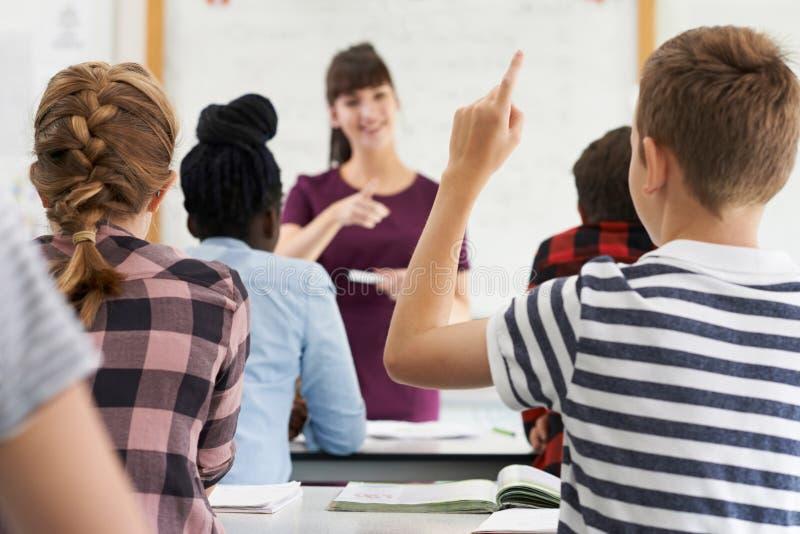 Αρσενικός εφηβικός μαθητής που απαντά στην ερώτηση στην κατηγορία στοκ εικόνα