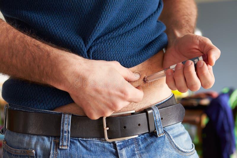 Αρσενικός διαβητικός που εγχέεται με την ινσουλίνη στοκ φωτογραφία