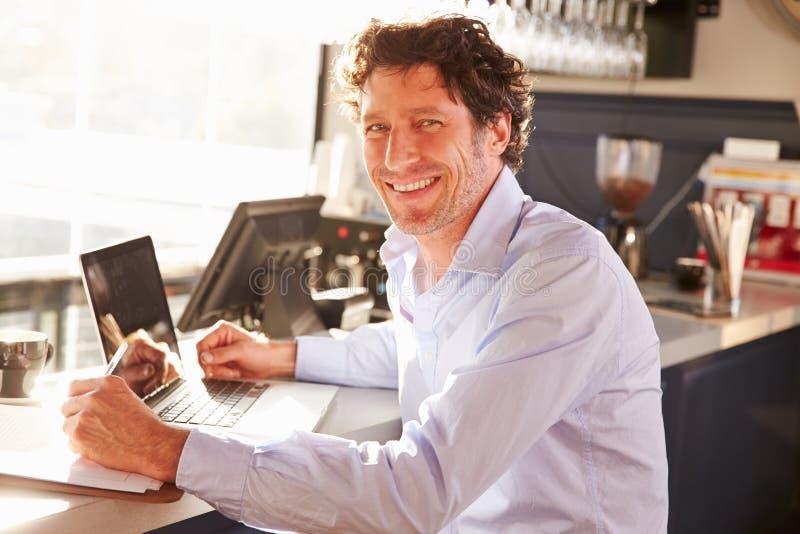 Αρσενικός διευθυντής εστιατορίων που εργάζεται στο lap-top στοκ φωτογραφία