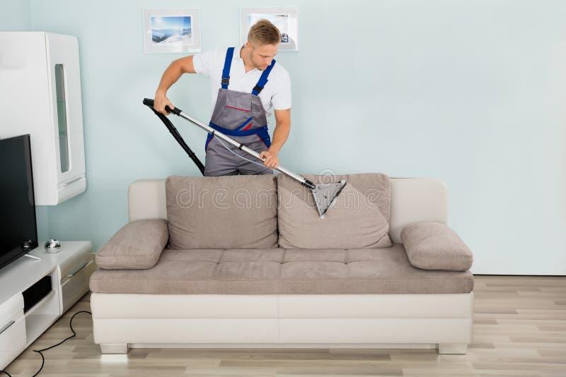 Αρσενικός καθαρίζοντας καναπές εργαζομένων με την ηλεκτρική σκούπα στοκ φωτογραφία