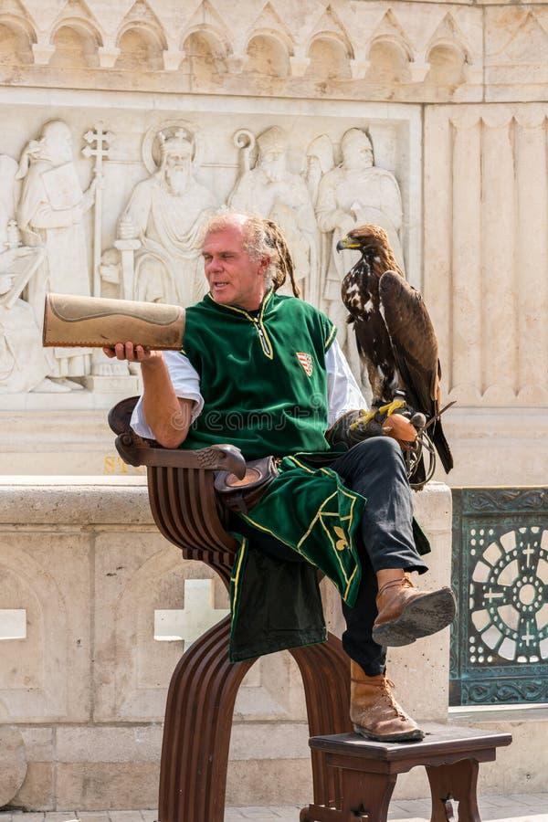Αρσενικός καλλιτέχνης οδών σε ένα plaza στη Βουδαπέστη Ουγγαρία που φορά ένα πράσινο παραδοσιακό κοστούμι που κρατά ένα πουλί του στοκ φωτογραφία