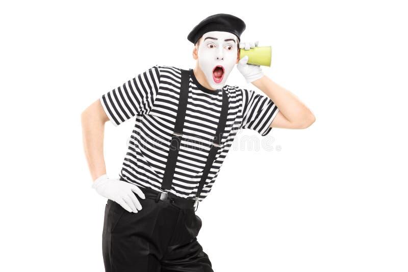 Αρσενικός καλλιτέχνης mime που ακούει μέσω του τοίχου με ένα φλυτζάνι στοκ εικόνες