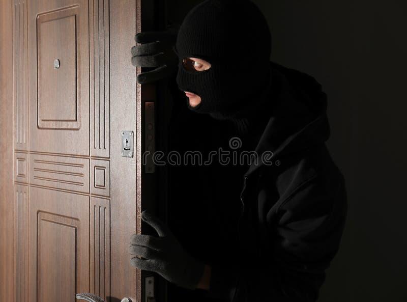 Αρσενικός κλέφτης που μπαίνει στο σπίτι μέσω της πόρτας τη νύχτα στοκ φωτογραφία