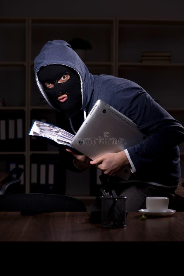 Αρσενικός κλέφτης balaclava στη νύχτα γραφείων στοκ φωτογραφία