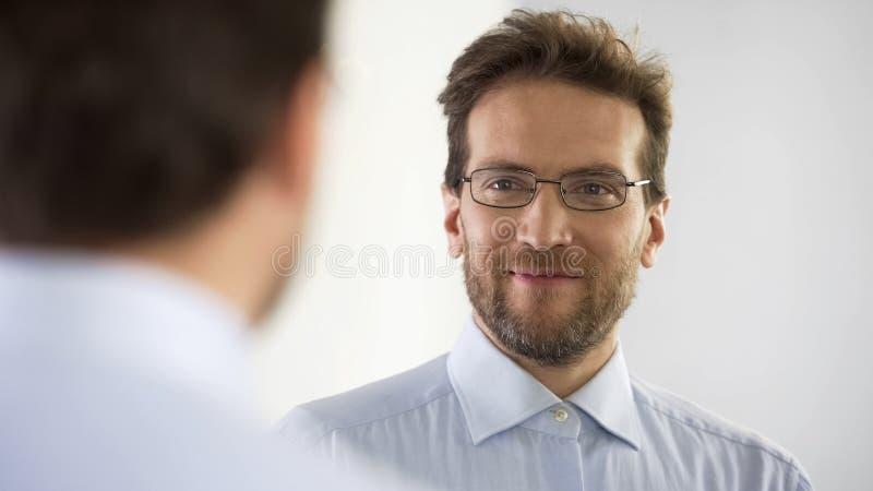 Αρσενικός λογιστής τραπεζών που κοιτάζει στον καθρέφτη με το χαμόγελο στο πρόσωπο, που προσπαθεί στα νέα γυαλιά στοκ φωτογραφίες