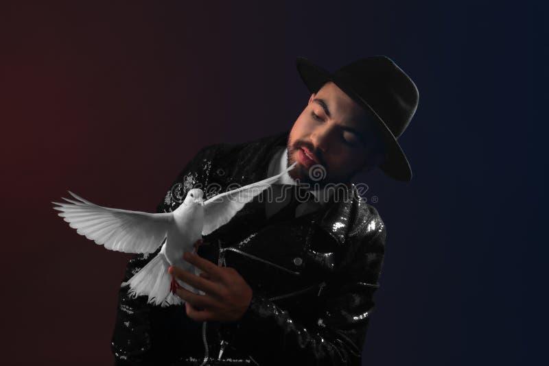Αρσενικός μάγος με το άσπρο περιστέρι στο σκοτεινό υπόβαθρο στοκ φωτογραφία