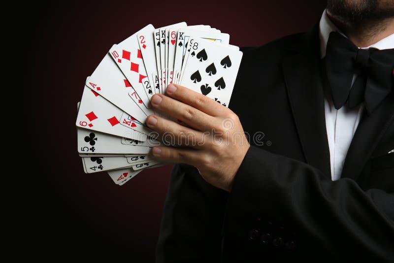 Αρσενικός μάγος που παρουσιάζει τεχνάσματα με τις κάρτες στο σκοτεινό υπόβαθρο, κινηματογράφηση σε πρώτο πλάνο στοκ φωτογραφία με δικαίωμα ελεύθερης χρήσης