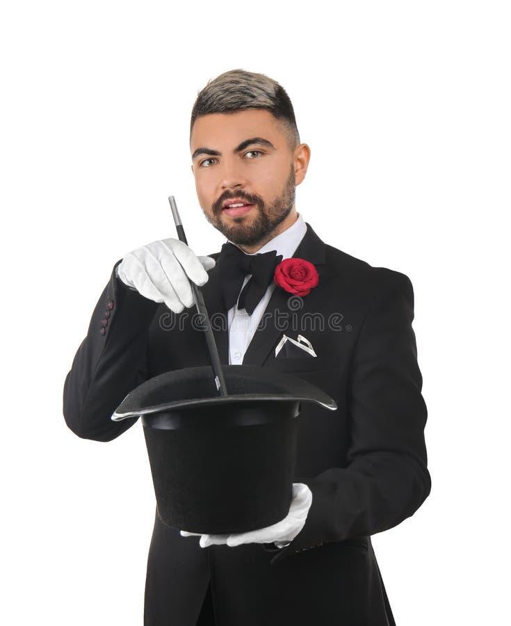 Αρσενικός μάγος που παρουσιάζει τεχνάσματα με το καπέλο στο άσπρο υπόβαθρο στοκ φωτογραφίες