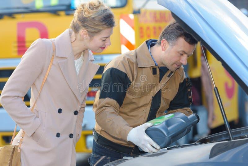 Αρσενικός μηχανικός γεμίζοντας πετρελαίου πελάτης γυναικών δεξαμενών όμορφος στοκ εικόνες