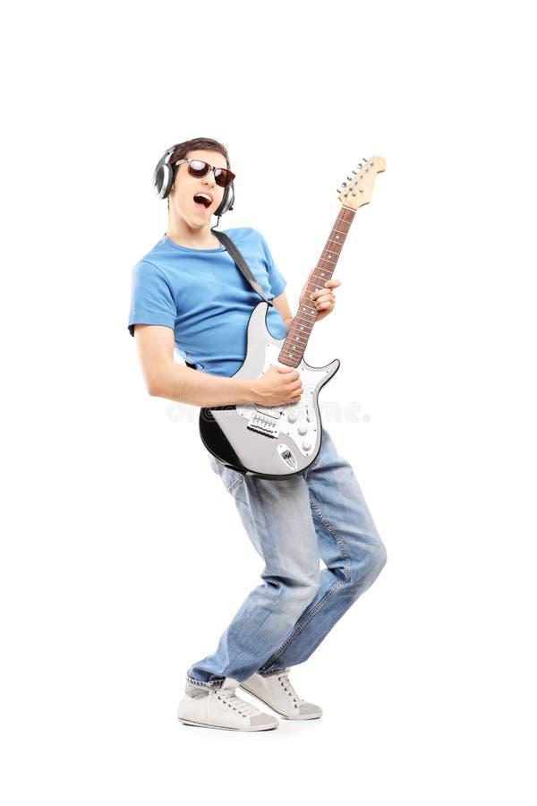 Αρσενικός μουσικός με τα ακουστικά που παίζει μια ηλεκτρική κιθάρα στοκ εικόνες