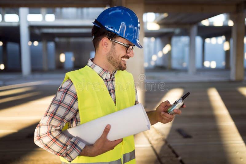 Αρσενικός νέος αρχιτέκτονας με τα σχεδιαγράμματα που χρησιμοποιούν walkie-talkie στοκ φωτογραφία με δικαίωμα ελεύθερης χρήσης