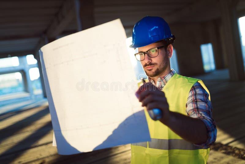 Αρσενικός νέος αρχιτέκτονας με τα σχεδιαγράμματα που χρησιμοποιούν walkie-talkie στοκ φωτογραφίες