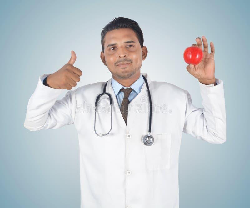 Αρσενικός νέος γιατρός που κρατά ένα κόκκινους μήλο και έναν αντίχειρα επάνω στοκ φωτογραφία με δικαίωμα ελεύθερης χρήσης