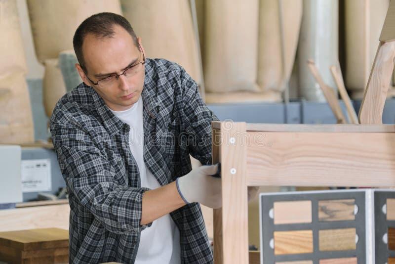 Αρσενικός ξυλουργός πορτρέτου στο ξύλινο εργαστήριο που κάνει την ξύλινη καρέκλα στοκ φωτογραφία