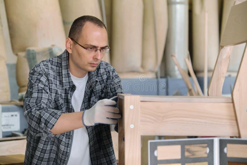 Αρσενικός ξυλουργός πορτρέτου στο ξύλινο εργαστήριο που κάνει την ξύλινη καρέκλα στοκ εικόνες με δικαίωμα ελεύθερης χρήσης