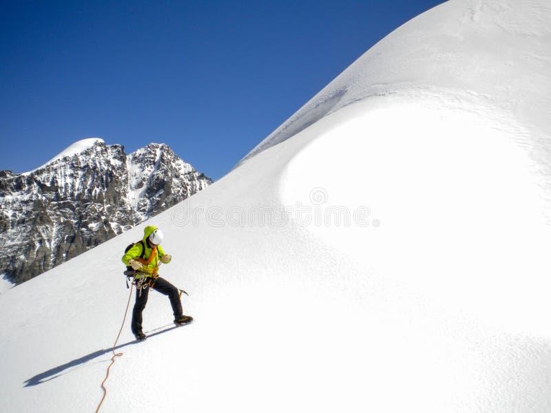 Αρσενικός οδηγός βουνών που στέκεται σε έναν παγετώνα στο δρόμο του σε μια υψηλή κορυφή στις ελβετικές Άλπεις στοκ φωτογραφίες