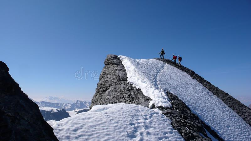 Αρσενικός οδηγός βουνών που φθάνει σε μια υψηλή αιχμή με δύο πελάτες μια όμορφη ημέρα στοκ φωτογραφία