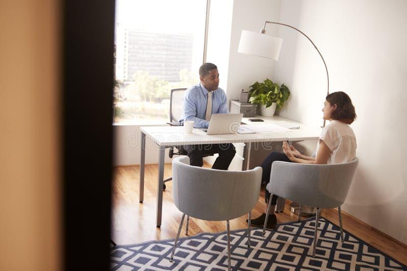 Αρσενικός οικονομικός σύμβουλος στη σύγχρονη συνεδρίαση γραφείων στο γραφείο που συναντά το θηλυκό πελάτη στοκ εικόνα
