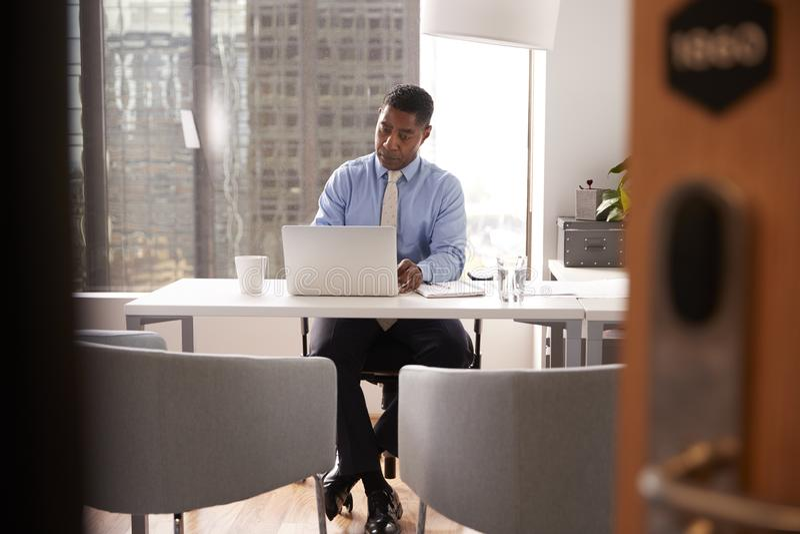 Αρσενικός οικονομικός σύμβουλος στη σύγχρονη συνεδρίαση γραφείων στο γραφείο που λειτουργεί στο lap-top στοκ εικόνα με δικαίωμα ελεύθερης χρήσης