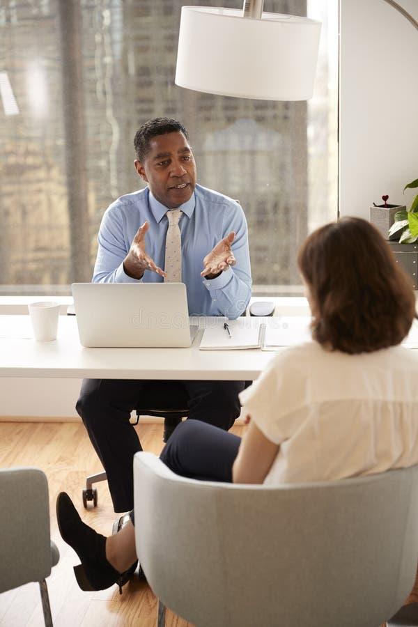 Αρσενικός οικονομικός σύμβουλος στη σύγχρονη συνεδρίαση γραφείων στο γραφείο που συναντά το θηλυκό πελάτη στοκ φωτογραφία