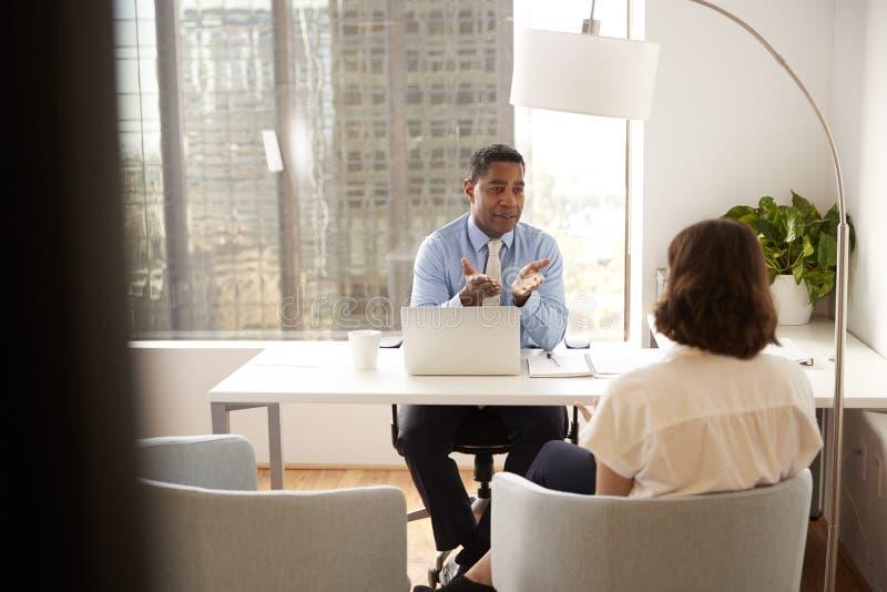Αρσενικός οικονομικός σύμβουλος στη σύγχρονη συνεδρίαση γραφείων στο γραφείο που συναντά το θηλυκό πελάτη στοκ εικόνες