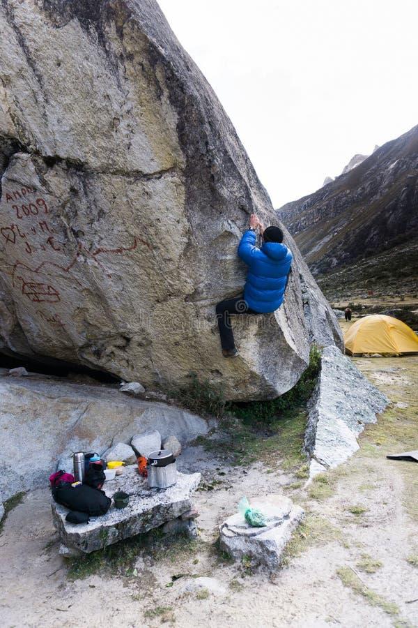 Αρσενικός ορειβάτης βουνών που αναρριχείται σε έναν λίθο highball σε ένα στρατόπεδο βάσεων στις Άνδεις στο Περού στοκ εικόνες