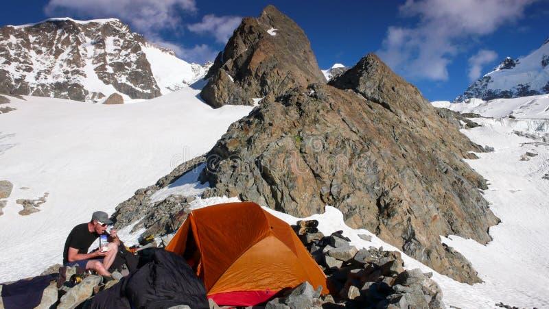 Αρσενικός ορειβάτης βουνών που τρώει στο στρατόπεδο βάσεων από μια πορτοκαλιά σκηνή με ένα θεαματικό τοπίο βουνών γύρω από τον στοκ εικόνα με δικαίωμα ελεύθερης χρήσης