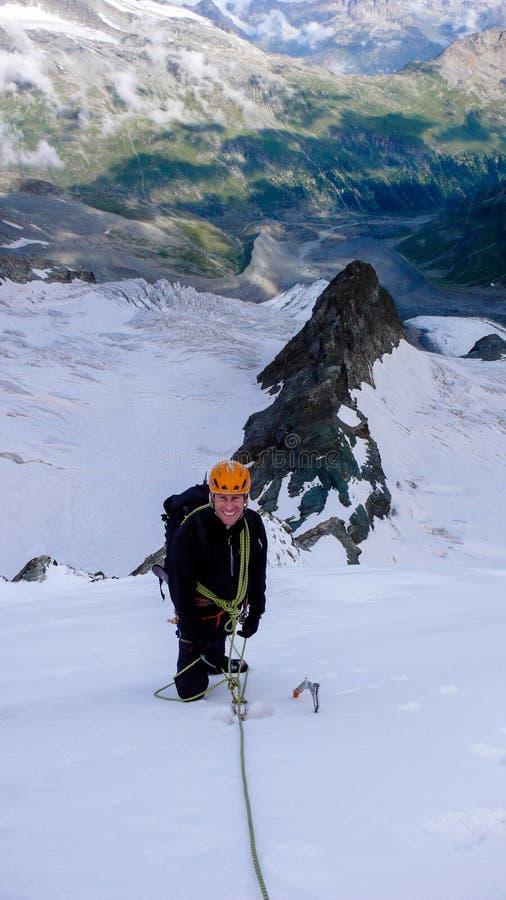 Αρσενικός ορειβάτης βουνών σε έναν υψηλό αλπικό παγετώνα με μια μεγάλη άποψη του φανταστικού τοπίου βουνών πίσω από τον στοκ εικόνα