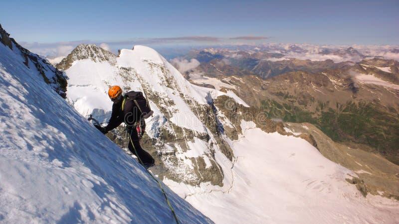 Αρσενικός ορειβάτης βουνών σε έναν υψηλό αλπικό παγετώνα με μια μεγάλη άποψη του φανταστικού τοπίου βουνών πίσω από τον στοκ φωτογραφία με δικαίωμα ελεύθερης χρήσης