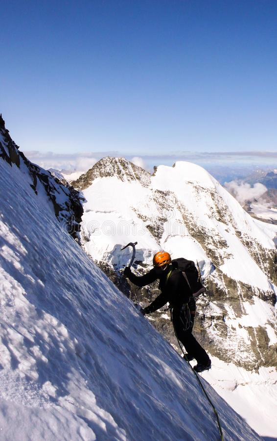 Αρσενικός ορειβάτης βουνών σε έναν υψηλό αλπικό παγετώνα με μια μεγάλη άποψη του φανταστικού τοπίου βουνών πίσω από τον στοκ φωτογραφίες