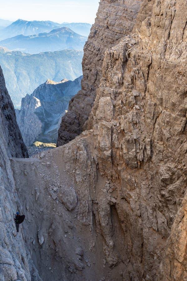 Αρσενικός ορειβάτης βουνών στο α μέσω Ferrata στο συναρπαστικό τοπίο των βουνών δολομιτών στην Ιταλία στοκ εικόνες