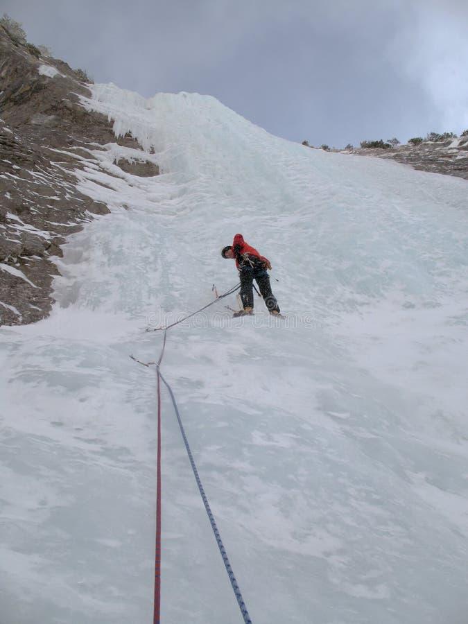 Αρσενικός ορειβάτης πάγου βουνών που αναρριχείται σε έναν απότομο και μακρύ παγωμένο καταρράκτη στις ελβετικές Άλπεις το βαθύ χει στοκ φωτογραφία με δικαίωμα ελεύθερης χρήσης